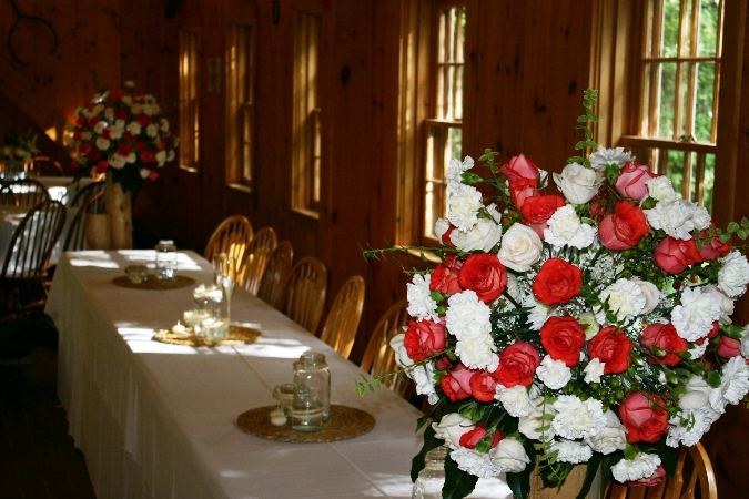 large white and red rose clusters at headtable using sawn logs as stands